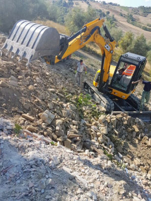 Digging on a Slant to reshape land behind a new house being built in Le Marche, Italy