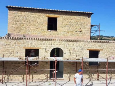Front with Wall Top Edge Decoration on a new stone house being built in Le Marche, Italy.