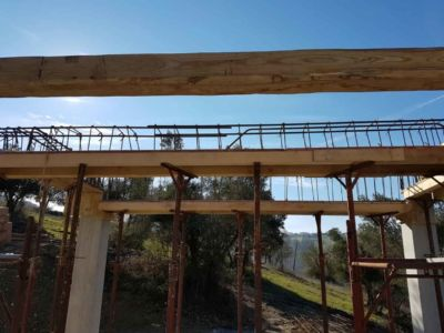 Chestnut Beam in Steel Structural Cage at a new house construction site in Le Marche