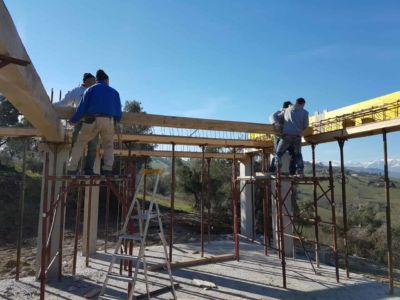 Placing a Beam: Mountains in Distance at a new house construction site in Le Marche