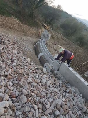 Laying Base of Wall Extension in front of a new house being built in Le Marche, Italy