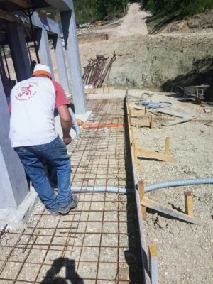 Preparing Sidewalk Form surrounding a new house being built in Le Marche