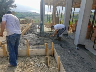 Spreading Concrete surrounding a new house being built in Le Marche