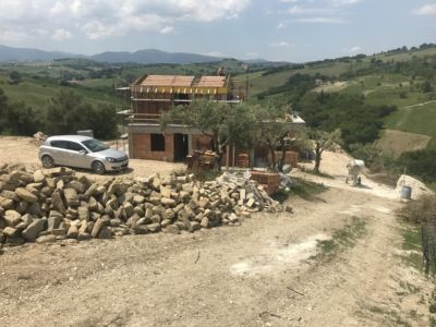 Stone and Olives in Front of a new house being built in Le Marche, Italy