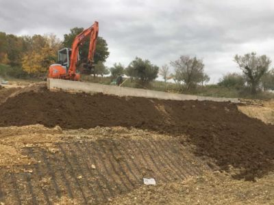 Working Above Retaining Wall in front of a new house being built in Le Marche, Italy