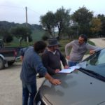 Italian neighbors signing contract on hood of car